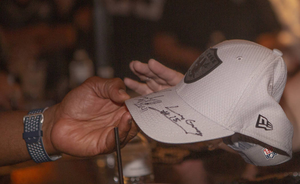 A autograph Oakland Raiders hat is signed for a fan at Linq Hotel and Casino on Monday, Sept. 9 ...