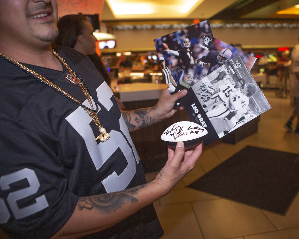 Steven Valtierra, shows off his Oakland Raiders signed cards and football during a fan autograp ...