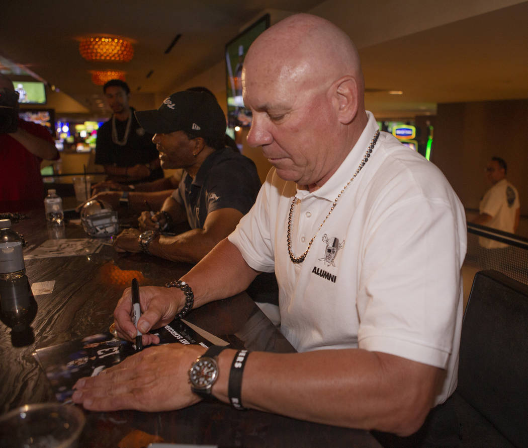 Former Oakland Raider Jay Schroeder signs a football for a fan at Linq Hotel and Casino on Mond ...