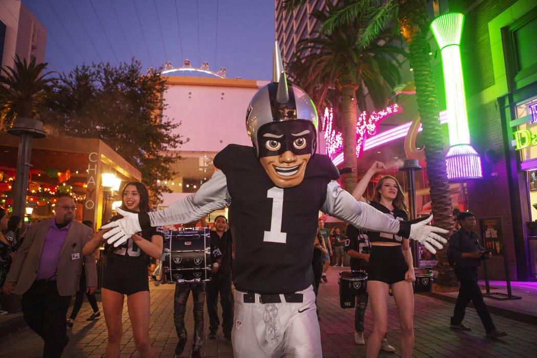 The Raiders mascot celebrates with Diana Tatevossian, left, and Kayla Kalisz, right, of Extreme ...