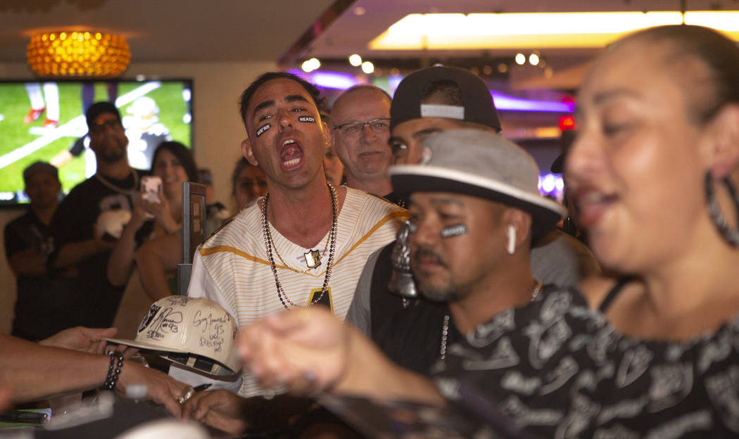 Chad Braden, from Los Angeles, celebrates before having his Raiders merchandise signed by forme ...