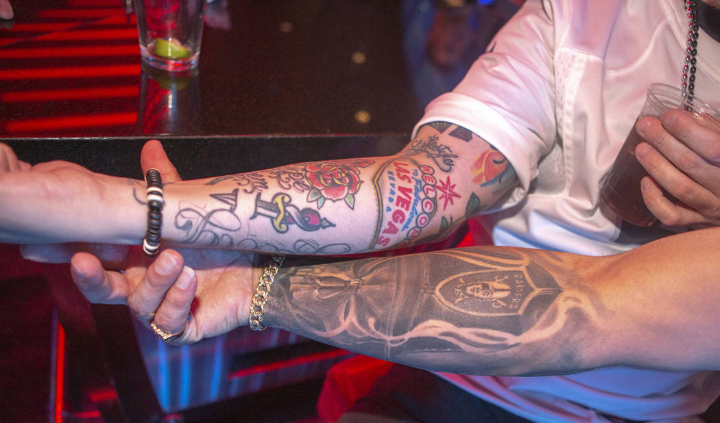 Kevin Petersen, shows his Las Vegas tattoo, as Chad Braden, shows off his Oakland Raiders tatto ...