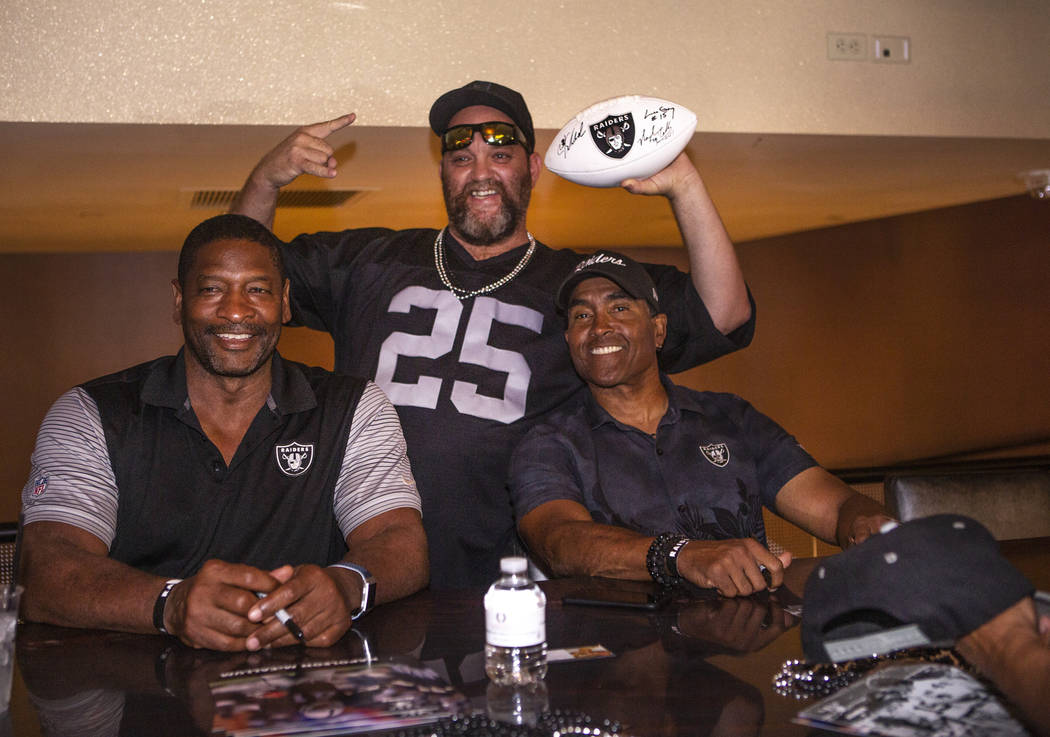 Tom Scannel, poses for a photo with former Oakland Raiders Napoleon Mccallum, right, and Leo Gr ...