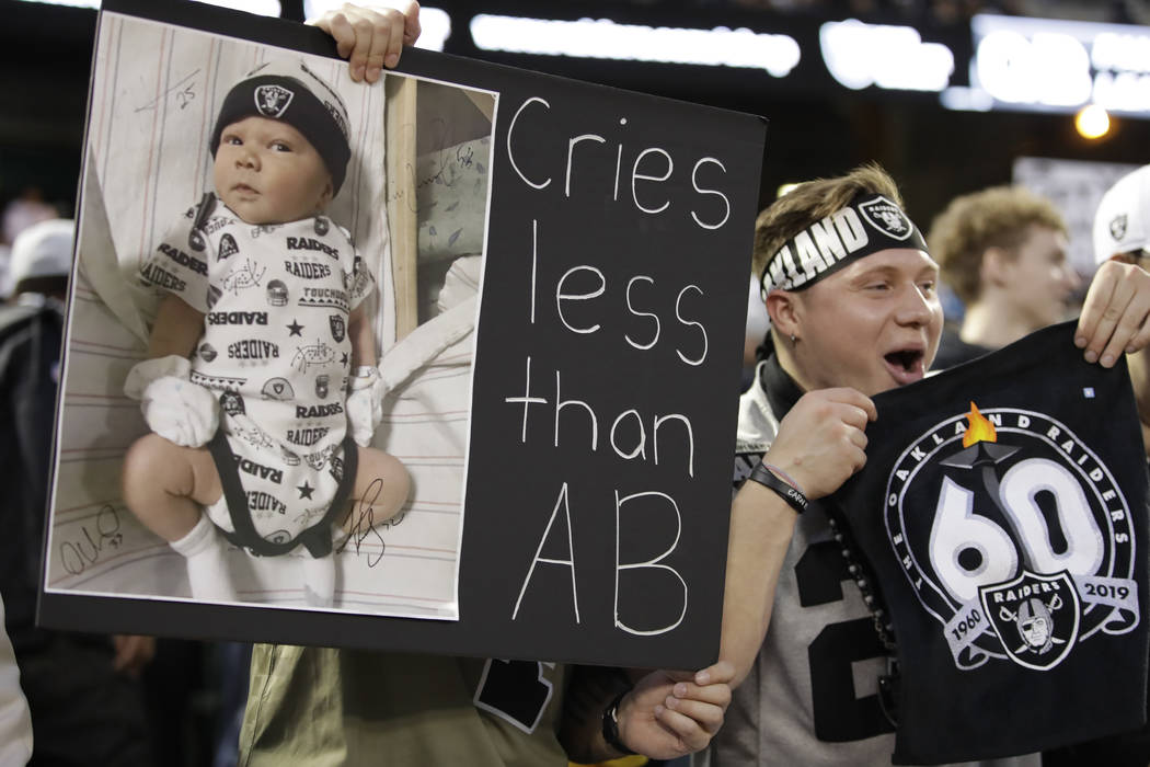 An Oakland Raiders cheers during the first half of an NFL football game against the Denver Bron ...