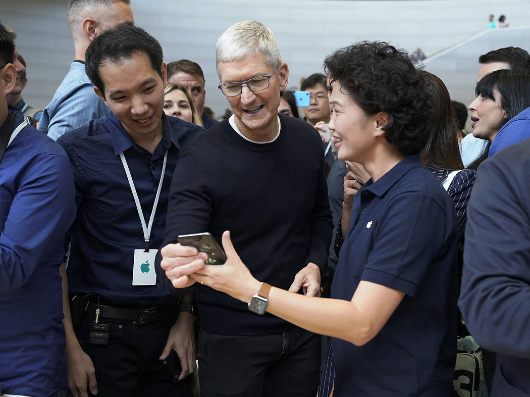 Apple CEO Tim Cook, center, looks at the the new iPhone 11 Pro Max, during an event to announce ...