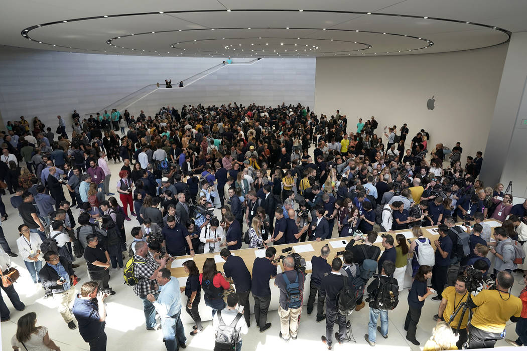 Event attendees get a look at the new products at the Steve Jobs Theater during an event to ann ...