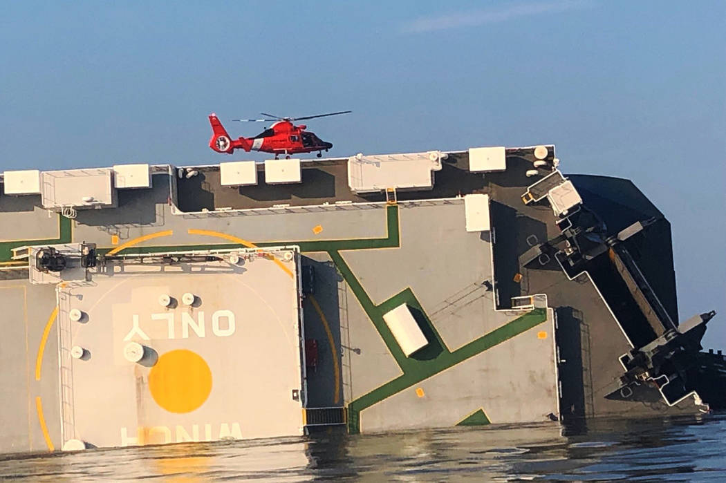 In this image released by the U.S. Coast Guard, a USCG helicopter hovers over an overturned car ...
