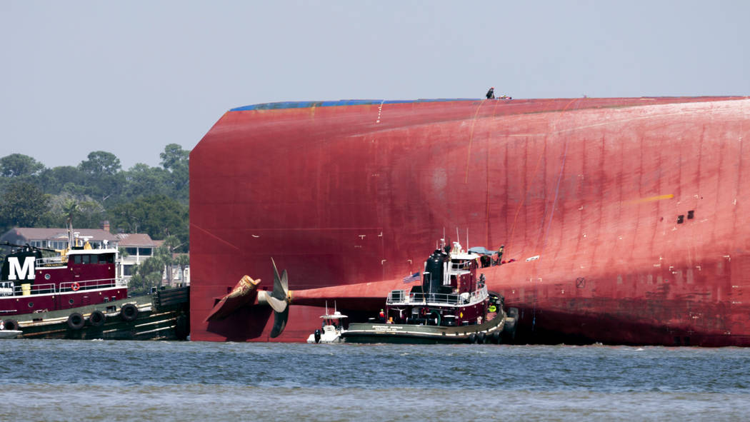 Rescuers work near the stern of the vessel Golden Ray as it lays on its side near the Moran tug ...