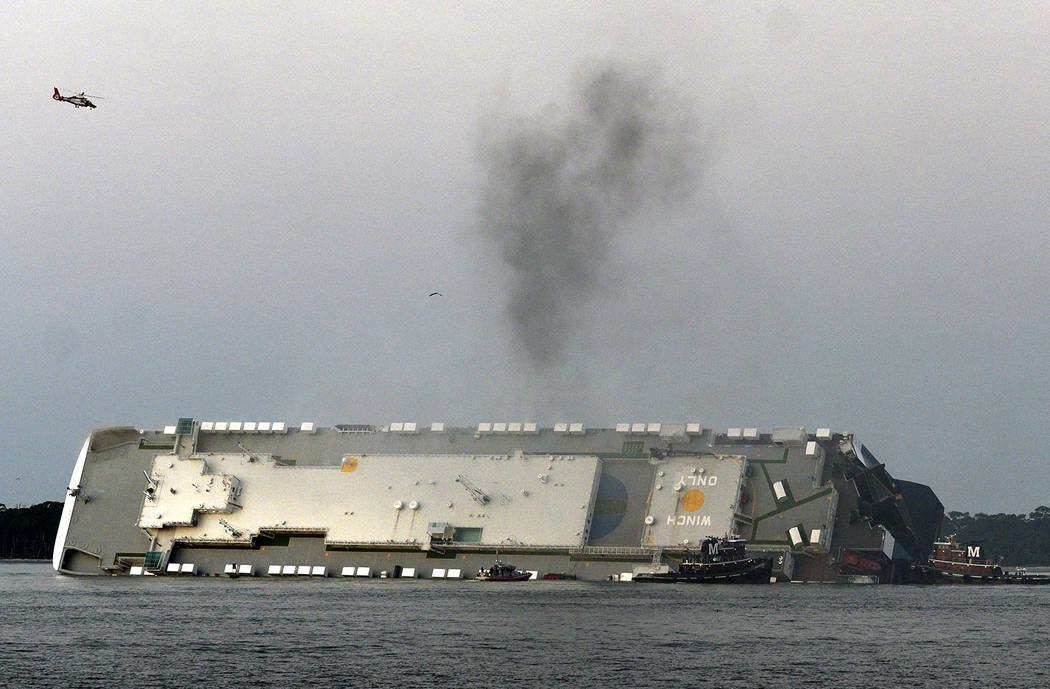 Smoke rises from a cargo ship that capsized in the St. Simons Island, Georgia sound Sunday, Sep ...