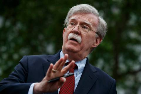 National security adviser John Bolton talks to reporters outside the White House in Washington, ...