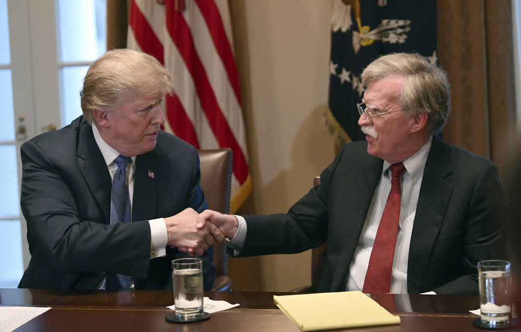 President Donald Trump, left, shakes hands with national security adviser John Bolton in the Ca ...