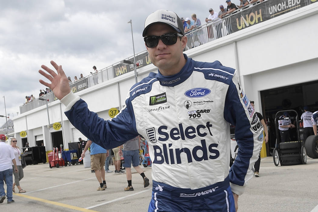 Driver David Ragan waves to fans while walking through the garage area during a practice sessio ...