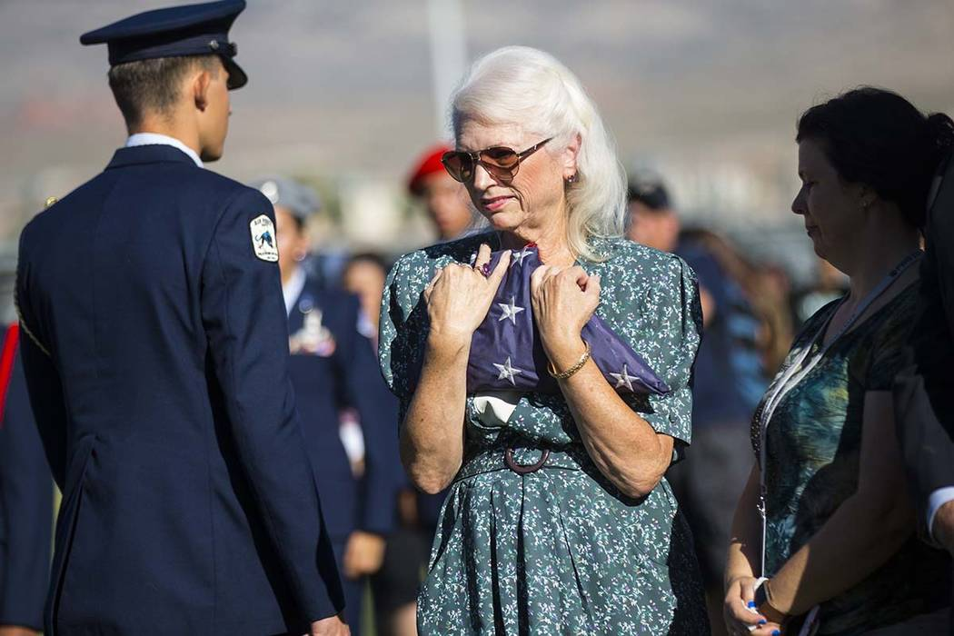 Retired teacher Gail Fahy holds the flag that was lowered and removed during the annual rededic ...
