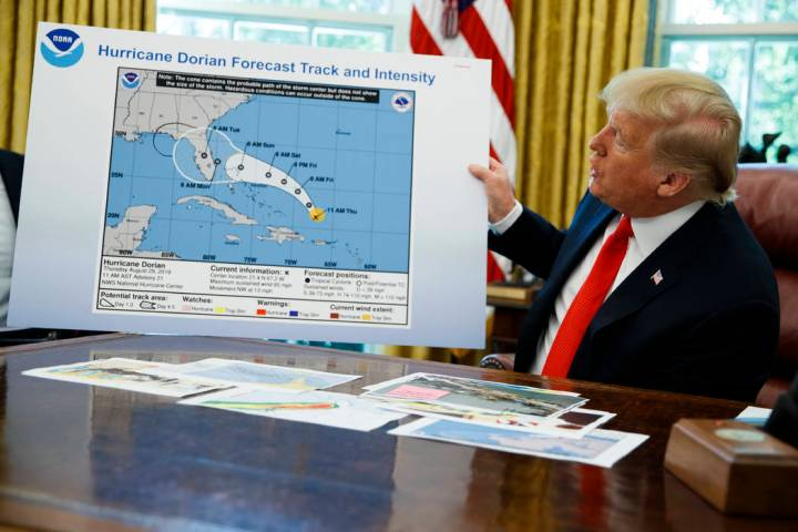President Donald Trump holds a chart as he talks with reporters after receiving a briefing on H ...