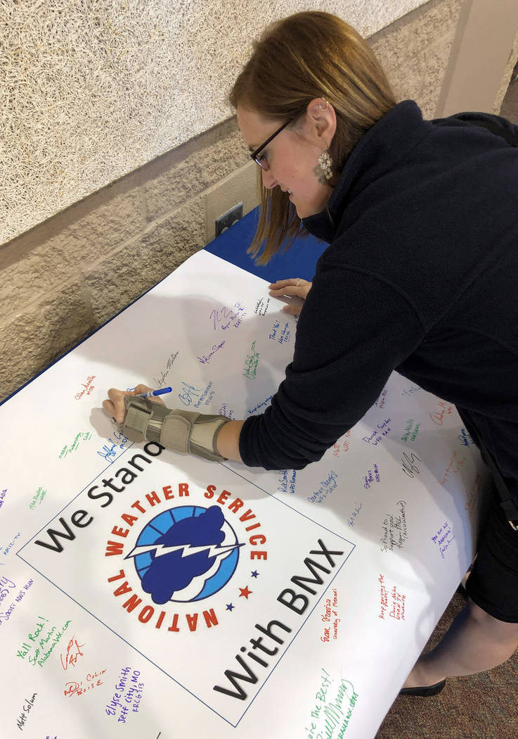 Christina Crowe signs a poster in support of the National Weather Service office in Birmingham, ...