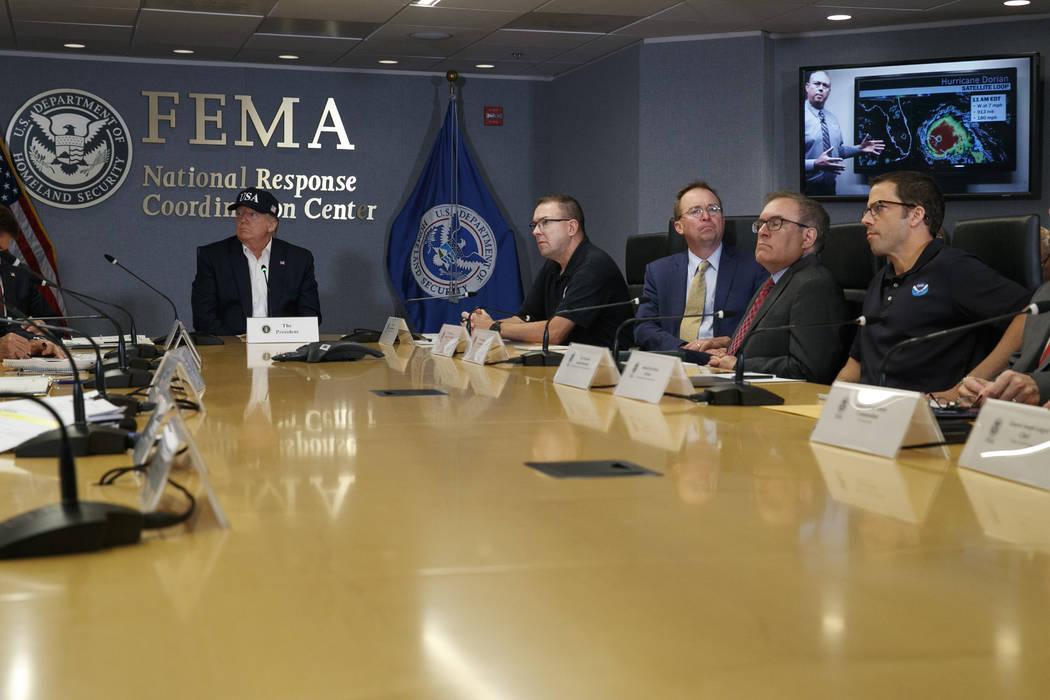 President Donald Trump, left, listens as Kenneth Graham, director of NOAA's National Hurricane ...