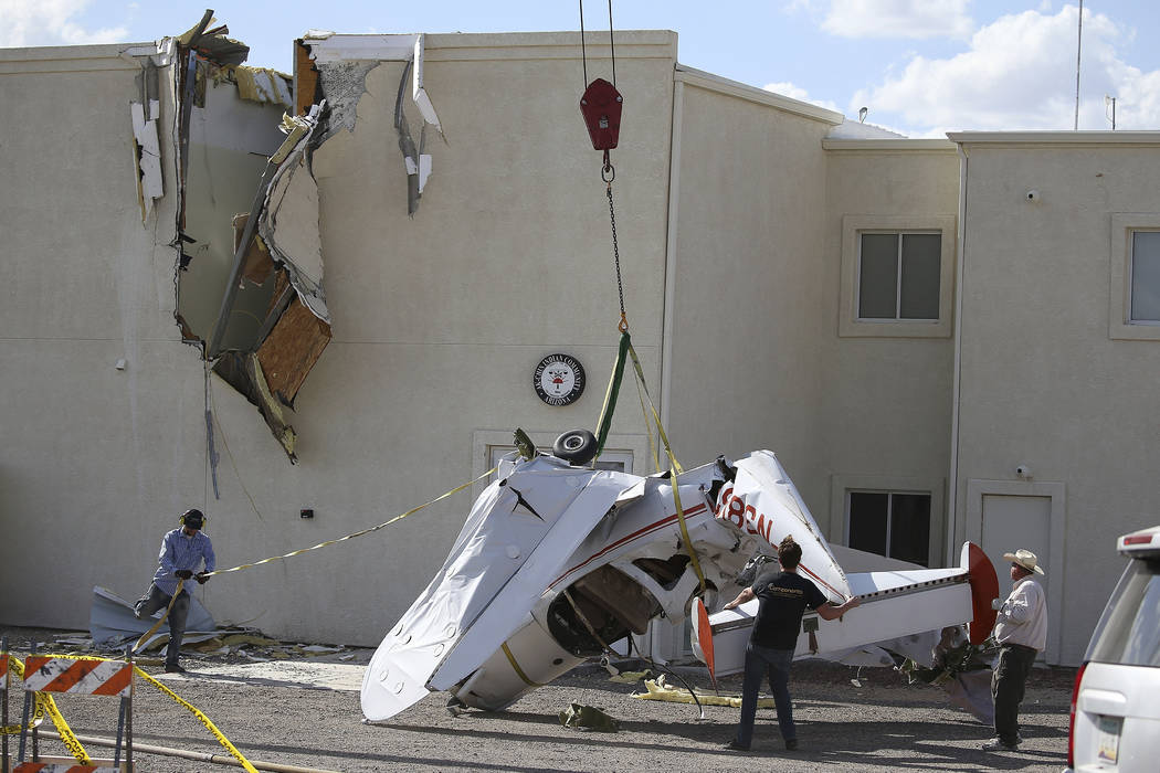 Workers set down a single-engine plane after it crashed into the terminal building shortly afte ...