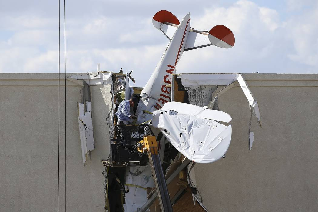 A worker pulls debris off a single engine plane prior to removal after it crashed into the term ...