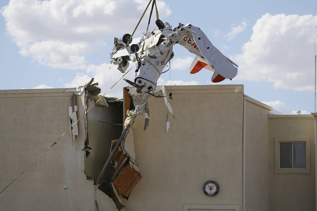 A single-engine plane is hoisted up after it crashed into the terminal building shortly after t ...