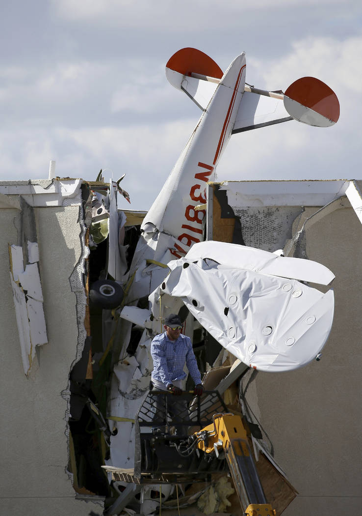A worker moves around a single-engine plane prior to removal after it crashed into the terminal ...
