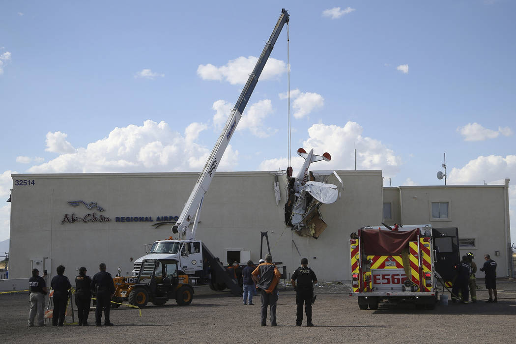 Police and fire personnel look on as workers remove a single-engine plane after it crashed into ...