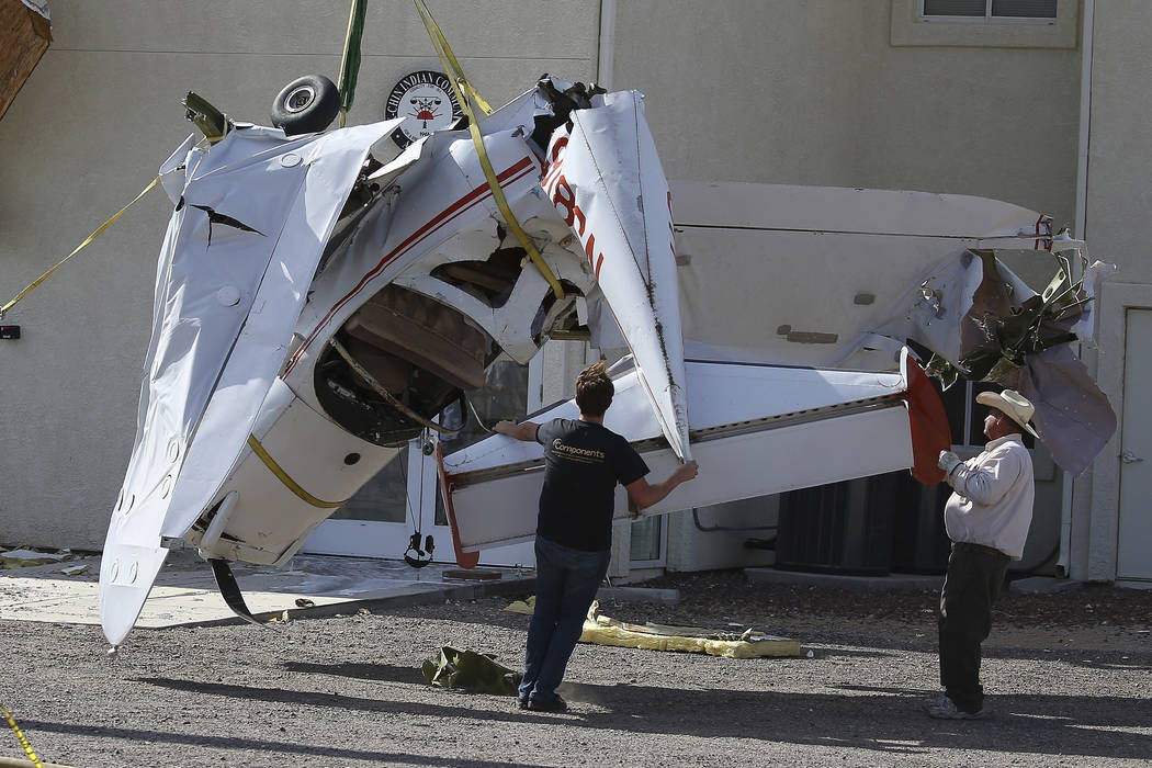 Workers guide a single-engine plane to the ground after it crashed into the terminal building s ...