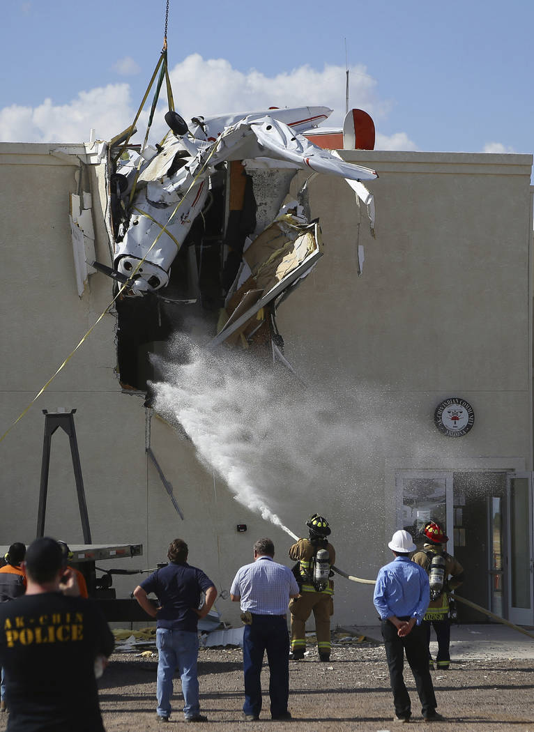 Fire personnel hose down the crash site as workers remove a single-engine plane after it crashe ...