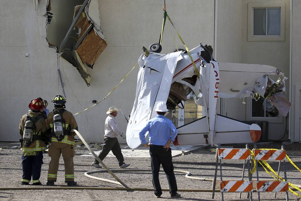 Workers remove a single-engine plane after it crashed into the terminal building shortly after ...