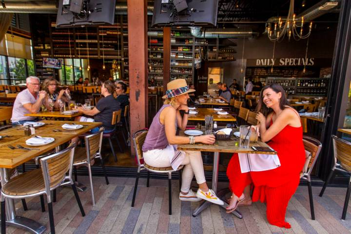 Customers Ryan Tselikis, center, and Olga McDowell, right, enjoy lunch on the deck at Grape Str ...
