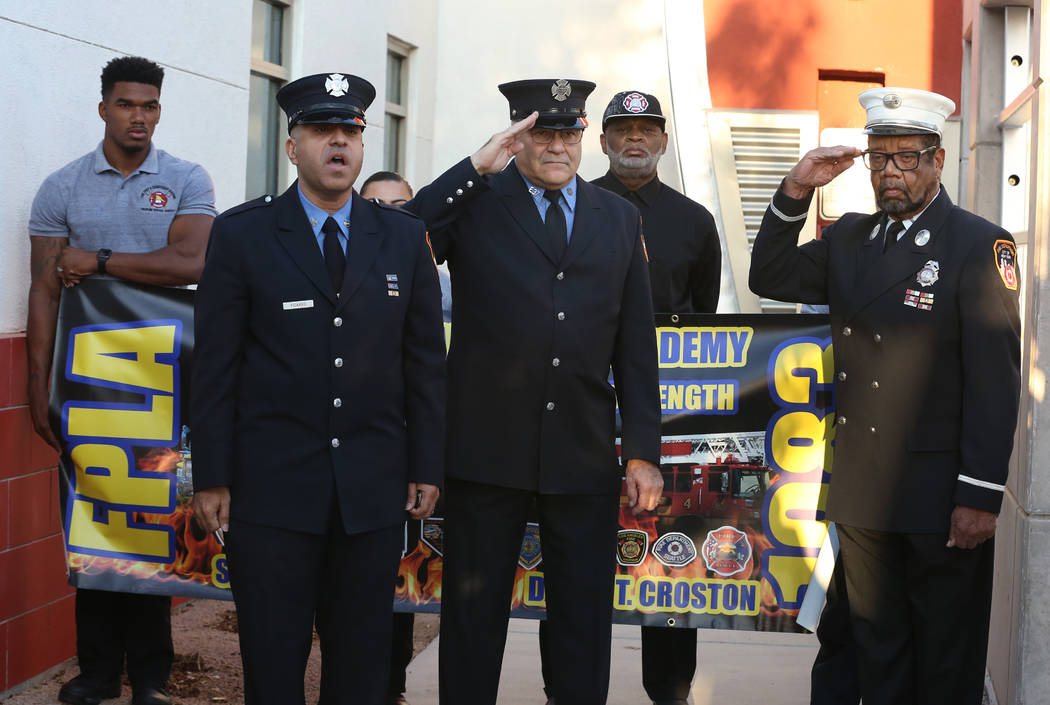 Frank Pizarro of Las Vegas, second left, a retired New York City firefighter, sings the Nationa ...