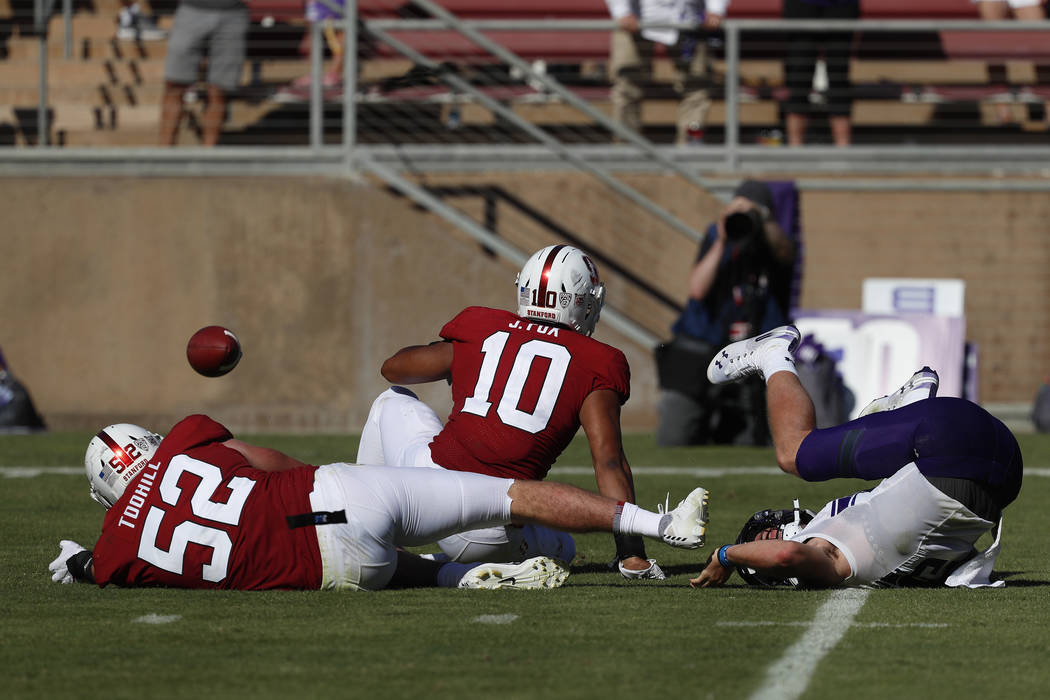 Stanford linebacker Casey Toohill (52) and Stanford linebacker Jordan Fox (10) cause a fumble a ...