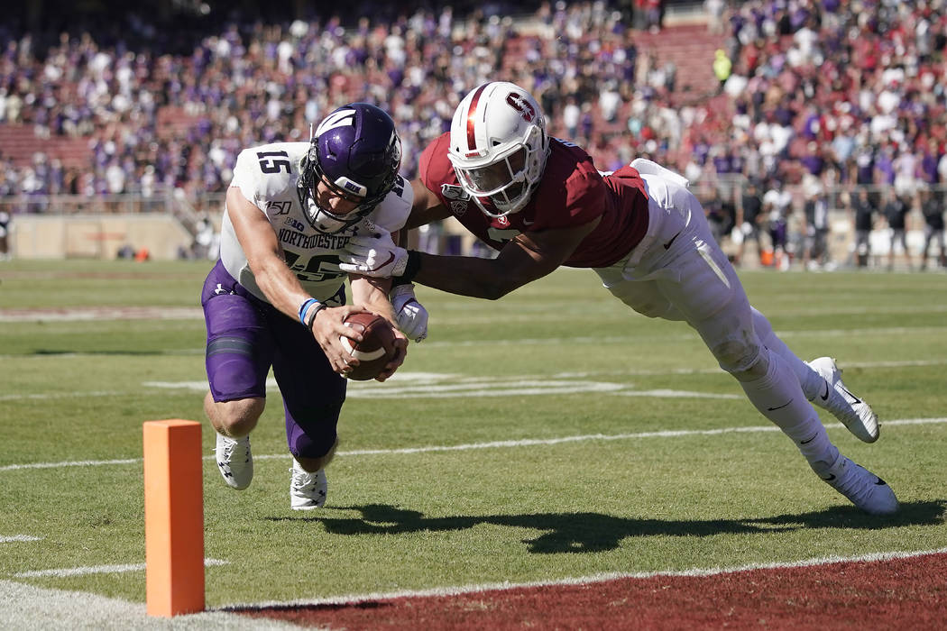 Northwestern quarterback Hunter Johnson (15) is stopped short of the end zone by Stanford lineb ...