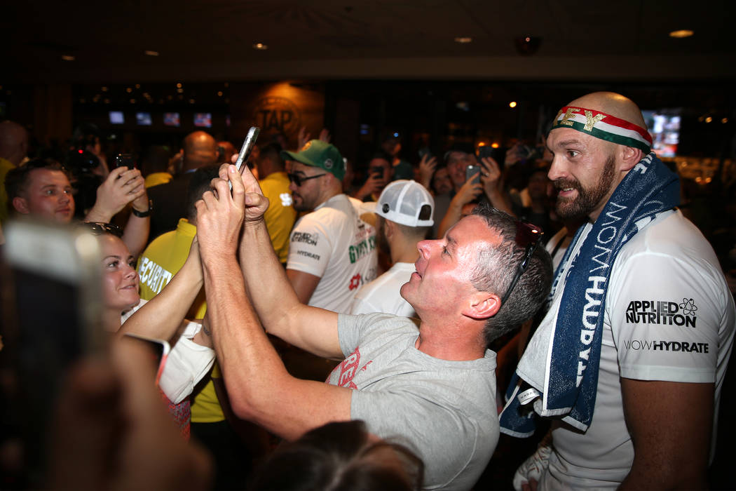 Heavyweight fighter Tyson Fury, right, takes a photo with fans following his open workout at th ...