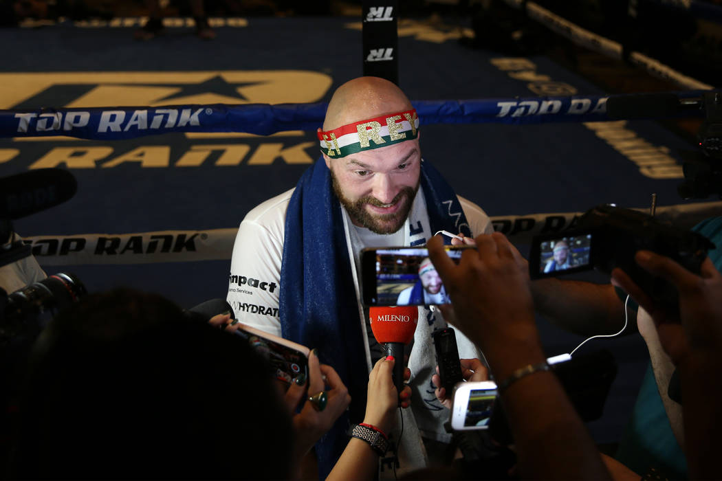 Heavyweight fighter Tyson Fury is interviewed by reporters following his open workout at the MG ...