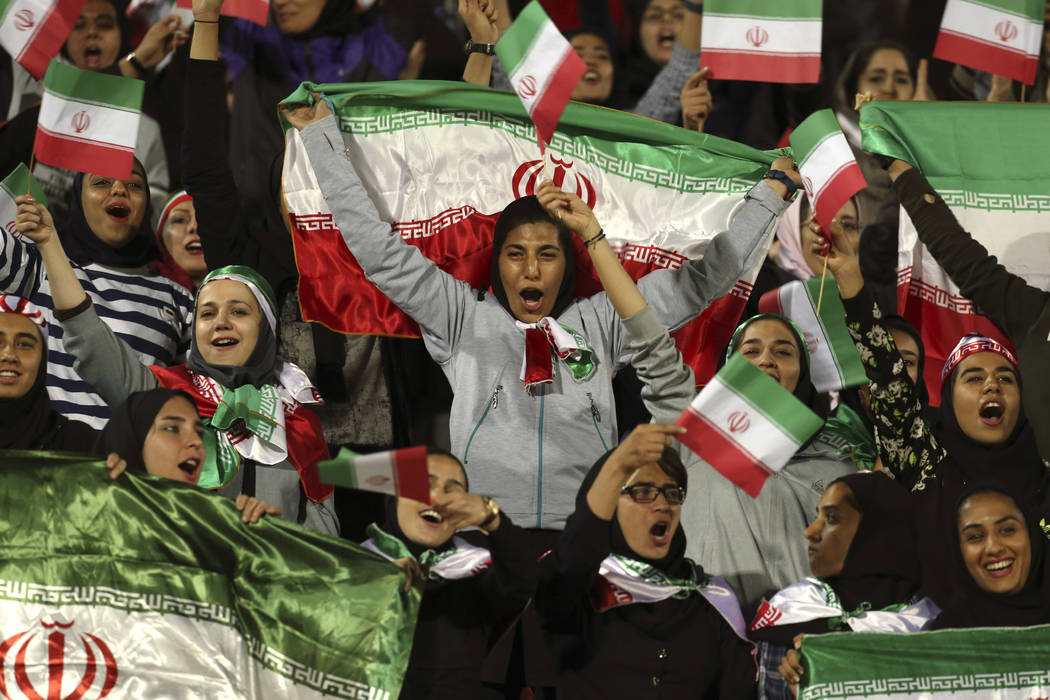 FILE - In this Oct. 16, 2018 file photo, Iranian women cheer as they wave their country's flag ...