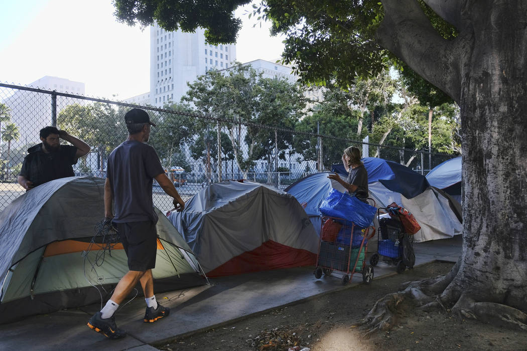FILE - In this Monday, July 1, 2019 file photo, homeless people move their belongings from a st ...