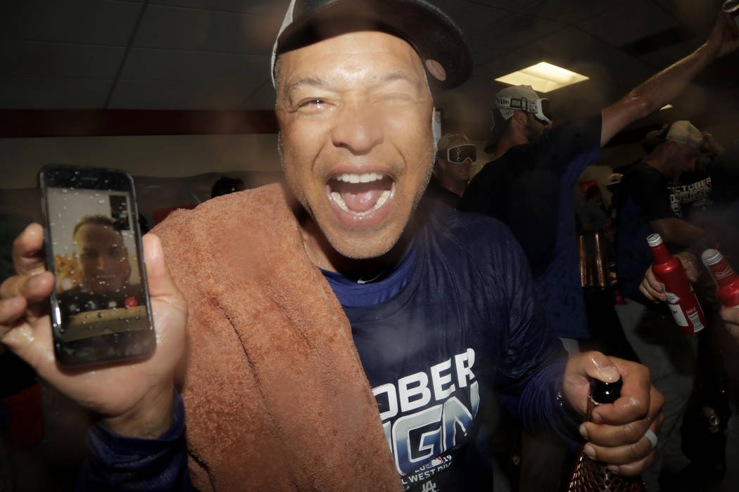 Los Angeles Dodgers manager Dave Roberts holds a cell phone during a video conference with inju ...
