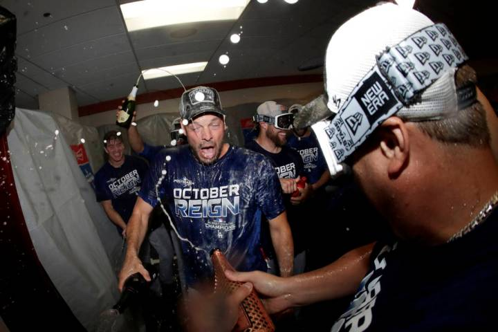 Los Angeles Dodgers pitcher Rich Hill, center, is doused during a lockerroom celebration after ...