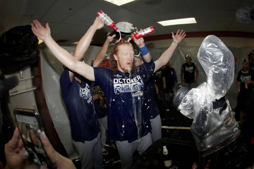 Los Angeles Dodgers pitcher Dustin May, center, is doused during a lockerroom celebration after ...
