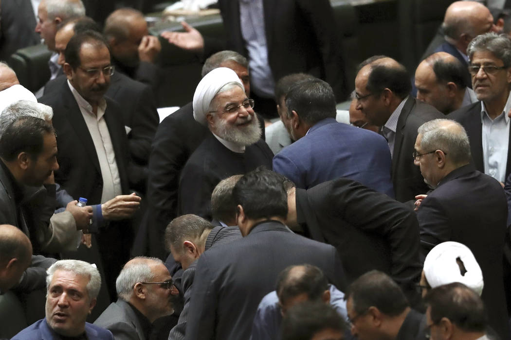 Iranian President Hassan Rouhani, center, listens to a lawmaker after defending his proposed to ...