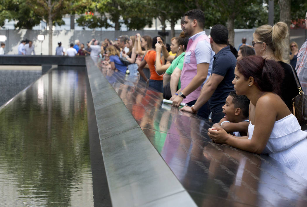 FILE- In this Sept. 9, 2015 file photo, visitors look at the waterfalls at the World Trade Cent ...