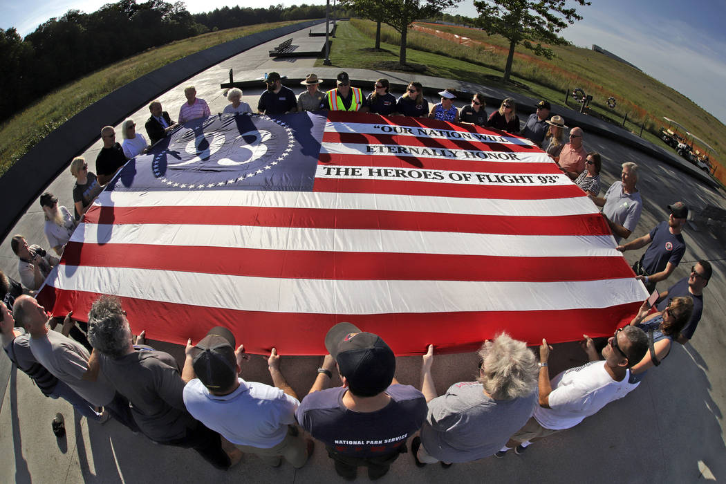 Visitors to the Flight 93 National Memorial in Shanksville, Pa., participate in a sunset memori ...