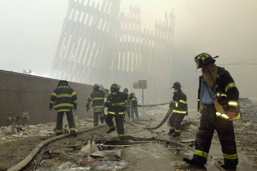 FILE - In this Sept. 11, 2001, file photo, firefighters work beneath the destroyed mullions, th ...