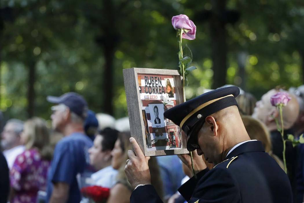 A man holds a photo of a victim during a ceremony marking the 18th anniversary of the attacks o ...