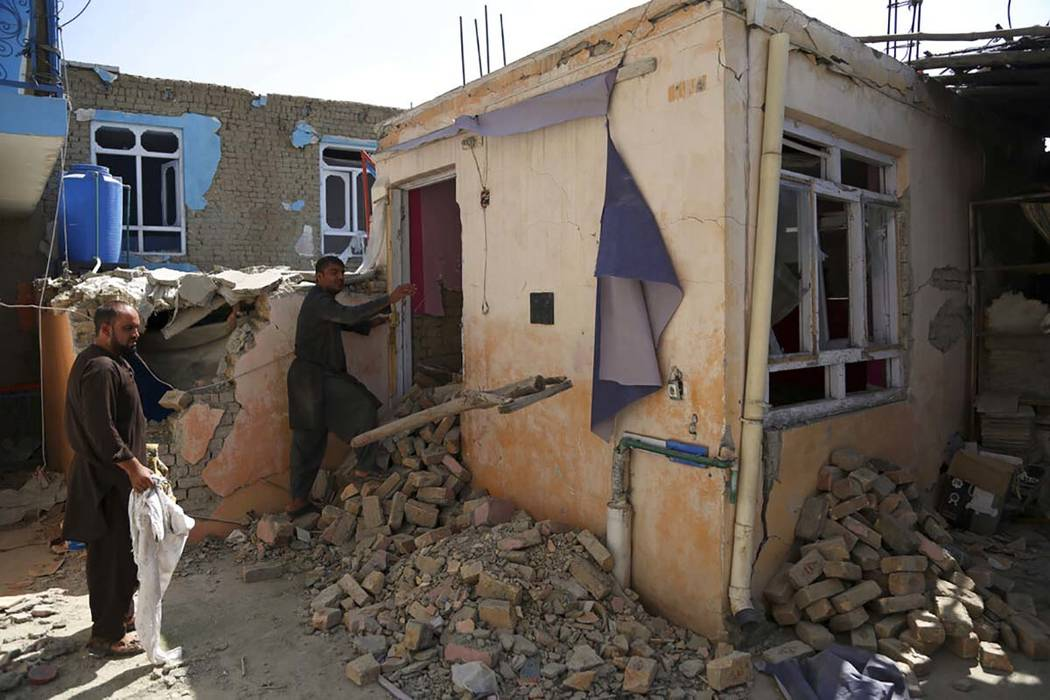 In a Tuesday, Sept. 10, 2019, photo, Afghans inspect their damaged house after a large explosio ...