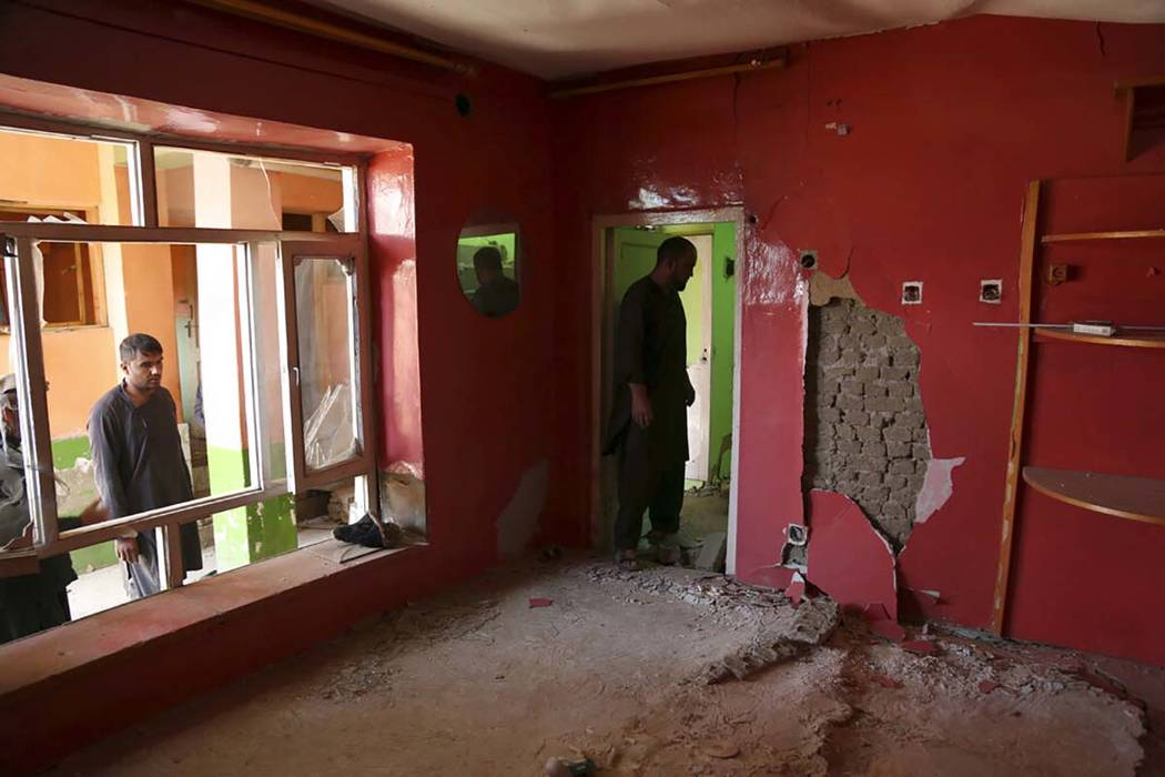 In this Tuesday, Sept. 10, 2019 photo, Afghans inspect their damaged house after a large explos ...