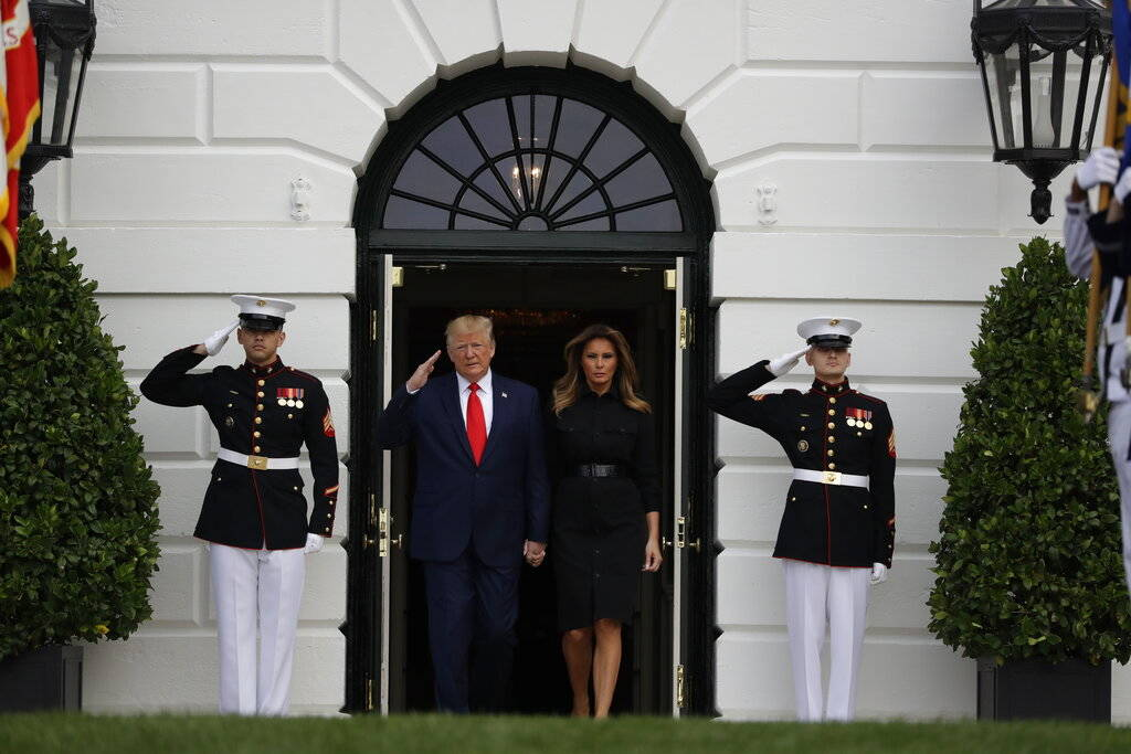President Donald Trump and first lady Melania Trump walk out to participate in a moment of sile ...