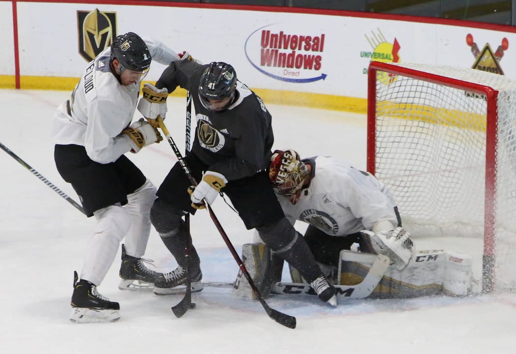 Golden Knights Zach Whitecloud, left, and goalie Maxime Lagace defend Pierre-Edouard Bellemare, ...