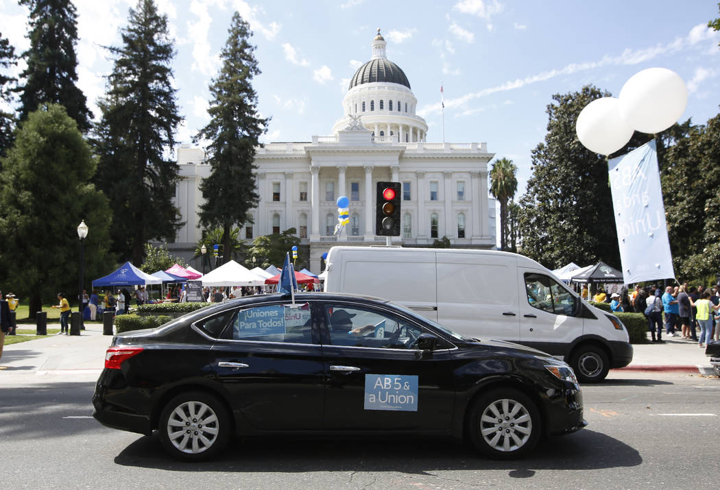 Dozens of supporters of a measure to limit when companies can label workers as independent cont ...