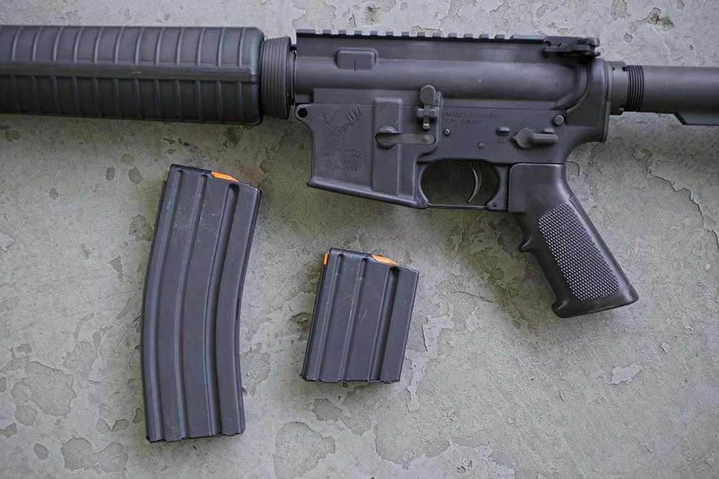 In this April 10, 2013, file photo, a stag arms AR-15 rifle with 30 round, left, and 10 round m ...